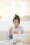 Femme ayant la céréale regardant l'ordinateur portable Image libre de droits