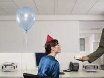 Femme ayant la fête d'anniversaire dans le bureau Photographie stock libre de droits