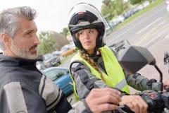 Femme ayant la leçon d'entraînement sur la moto photo stock