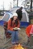 Femme ayant la nourriture au feu de camp Image stock