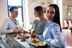 Femme ayant la nourriture avec des amis au compteur de barre Image stock