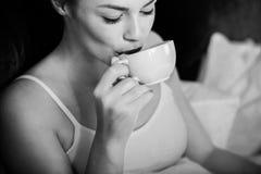 Femme ayant le café de matin dans le lit, noir et blanc image libre de droits