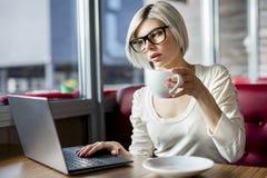 Femme ayant le café tout en travaillant sur l'ordinateur portable en café image stock