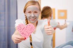 Femme ayant le masque protecteur gris tenant l'éponge de coeur Images stock