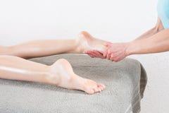 Femme ayant le massage de pieds dans le salon de beauté image stock