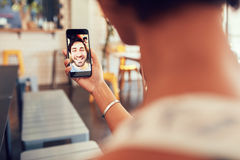 Femme ayant un appel visuel avec l'homme à son téléphone intelligent Images libres de droits