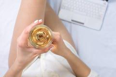 Femme ayant un verre de vin dans le lit image stock