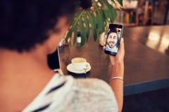 Femme ayant un videochat avec l'ami au téléphone portable Image libre de droits