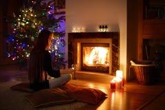 Femme ayant une boisson par une cheminée dans a sur Noël Photos stock
