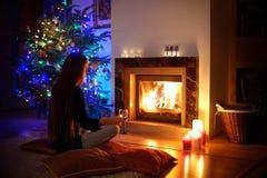Femme ayant une boisson par une cheminée dans a sur Noël Photographie stock libre de droits
