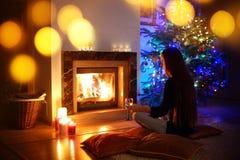 Femme ayant une boisson par une cheminée dans a sur Noël Images libres de droits