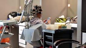 Femme ayant une permanente et recherchant la photo sur le téléphone portable banque de vidéos