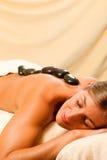 Femme ayant une session de thérapie en pierre chaude Photographie stock libre de droits