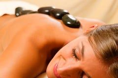 Femme ayant une session de thérapie en pierre chaude Photographie stock