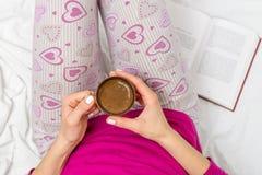 Femme ayant une tasse de café dans le lit Image libre de droits