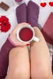 Femme ayant une tasse de thé dans le lit Photos libres de droits