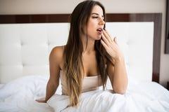 Femme baîllant dans le lit à la maison images stock