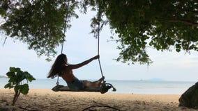 Femme balançant à la plage tropicale, jour ensoleillé, temps beau Oscillation en île de paradis banque de vidéos