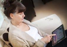 Femme belle d'âge d'admission à la pension recherchant dans l'Internet sur le dispositif de comprimé Images libres de droits