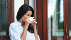 Femme belle de brune buvant du thé ou du café chaud tenant la tasse blanche de porcelaine à la main banque de vidéos