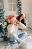 Femme belle lui donnant le boyriend un cadeau à la maison célébrant des personnes de nouvelle année Image stock
