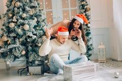 Femme belle lui donnant le boyriend un cadeau à la maison célébrant des personnes de nouvelle année Image libre de droits