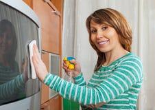 Femme belle nettoyant la TV images stock