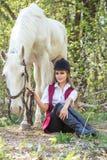 Femme belle s'asseyant au sol avec le cheval brun près de elle Photos stock
