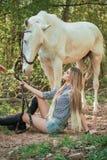 Femme belle s'asseyant au sol avec le cheval brun près de elle Photo libre de droits