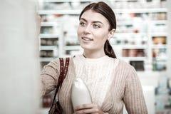 Femme belle souriant tout en faisant des emplettes dans le magasin de pharmacie le week-end image stock