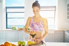 Femme bien faite d'ajustement préparant le jus de fruit frais Photographie stock libre de droits