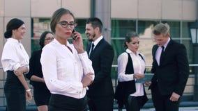Femme blanche et blonde d'affaires ayant un entretien important sur le téléphone et les gens d'affaires se tenant dans clips vidéos