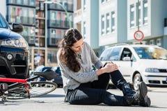 Femme blessée éprouvant la douleur sévère provoquée par entorse de genou à l'arrière photographie stock libre de droits