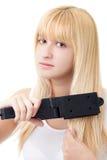 Femme blond avec le redresseur de cheveu Images stock