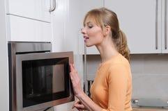 Femme blond avec une micro-onde photographie stock libre de droits