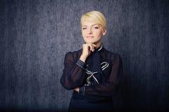 Femme blond d'affaires dans le sourire noir de subsistance de procès Image stock