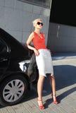 Femme blond près d'automobile noire Photographie stock