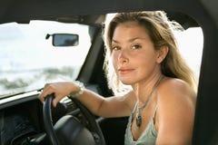 Femme blond s'asseyant dans le véhicule images libres de droits
