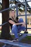 Femme blond s'asseyant dans les gradins au soleil Photo libre de droits