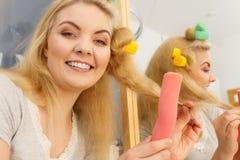 Femme blonde à l'aide des rouleaux de cheveux image stock