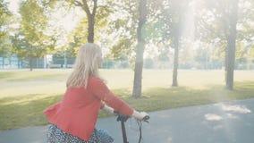 Femme blonde à la mode active montant un vélo en parc au coucher du soleil Beau jour pour un tour clips vidéos