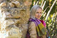 femme blonde à la mode près d'un mur en pierre en parc de ville Image stock