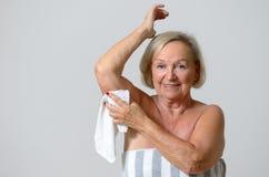 Femme blonde âgée par milieu rasant son aisselle Photo stock