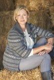 Femme blonde âgée par milieu s'asseyant sur Hay Bale Photos stock