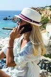 Femme blonde élégante souriant et à l'aide du smartphone Photo stock