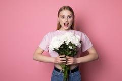 Femme blonde ?tonn?e par jeunes avec la bouche ouverte utilisant le T-shirt rose avec les fleurs blanches dans des mains photo stock