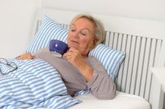 Femme blonde adulte sur son lit tenant sa tasse Photo stock