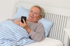 Femme blonde adulte sur son lit tenant son téléphone portable Photographie stock libre de droits