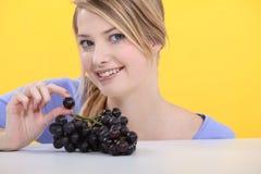 Femme blonde affichant des raisins photos stock