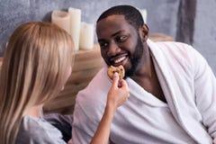 Femme blonde alimentant son ami africain avec des biscuits Image libre de droits